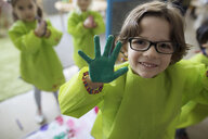 Portrait smiling, confident preschool boy in smock showing finger paint on hands - HEROF16019