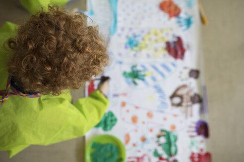Preschool boy finger painting at poster - HEROF16022