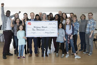 Portrait enthusiastic community with large donation check cheering in community center - HEROF16034