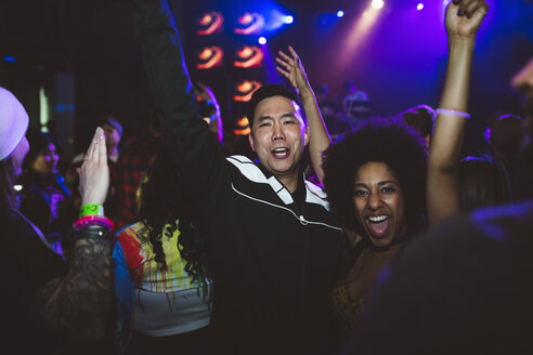 Portrait enthusiastic, fun young millennial couple cheering, dancing in nightclub - HEROF16043