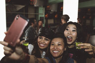 Playful, exuberant young female millennial friends taking shots and taking selfie in nightclub - HEROF16058