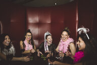 Playful, carefree young female millennial friends drinking, enjoying bachelorette party at nightclub - HEROF16061