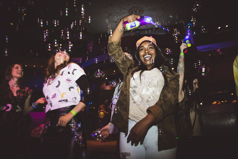Playful, exuberant young female millennial with bubble maker dancing in nightclub - HEROF16064