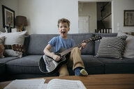 Portrait playful boy playing guitar on living room sofa - HEROF16082