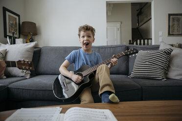 Portrait playful boy playing guitar on living room sofa - HEROF16082