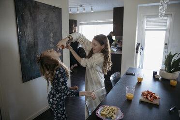 Playful sisters in pajamas enjoying spray whip cream at dining table - HEROF16085