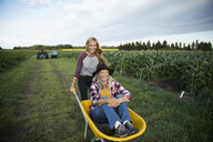 Blonde daughter farmer pushing mother in wheelbarrow on farm - HEROF16106