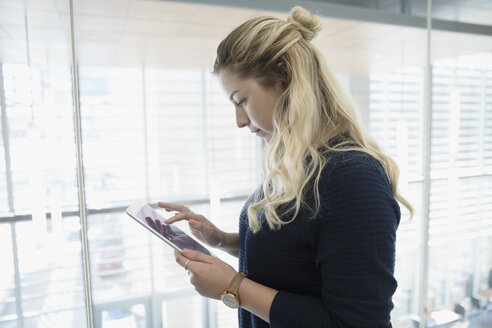 Blonde businesswoman using digital tablet - HEROF16115