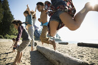 Boy and girl friends jumping over log on sunny beach - HEROF16208