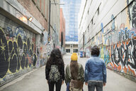 Young friends standing in urban alley with graffiti - HEROF16244