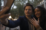 Young couple with camera phone taking selfie with engagement ring - HEROF16259