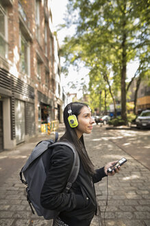 Young woman with backpack and headphones listening to music with smart phone on urban sidewalk - HEROF16268