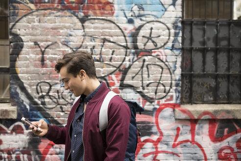 Young man texting with smart phone along urban graffiti wall - HEROF16274