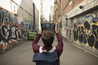 Young man with digital tablet camera photographing urban graffiti alley - HEROF16280