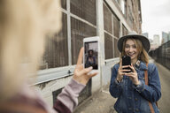 Young women friends taking selfies with camera phones face to face on urban street - HEROF16286