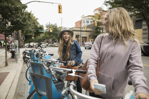 Young women friends using bicycle sharing system on urban street - HEROF16292