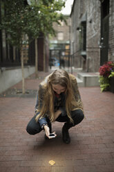 Young woman with camera phone photographing autumn leaf on urban sidewalk - HEROF16298