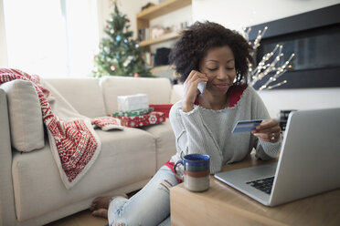 Woman with credit card talking on smart phone, Christmas shopping at laptop in living room - HEROF16319