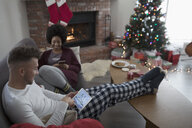 Young couple in pajamas relaxing, using digital tablet near fire in Christmas living room - HEROF16337