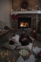 Young couple in pajamas laying, relaxing by fire near Christmas tree in living room - HEROF16343