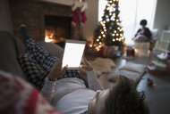 Young man in pajamas relaxing, using digital tablet near fire and Christmas tree in living room - HEROF16349