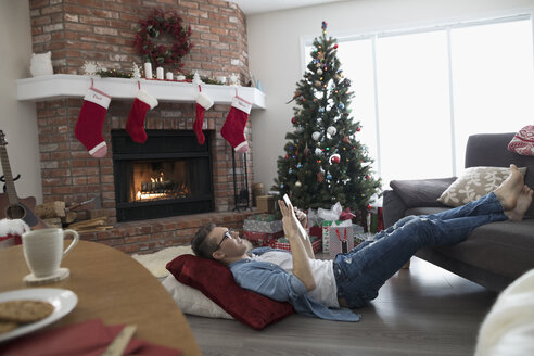 Young man relaxing, using digital tablet on floor in Christmas living room - HEROF16352