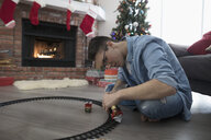 Young man assembling train tracks on floor near fireplace in Christmas living room - HEROF16355