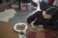 Teenage girl writing letter to Santa in Christmas living room - HEROF16358