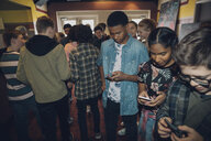Tween boys and and girls texting with smart phones in movie theater lobby - HEROF16367