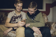 Tween boys texting with smart phone, hanging out on sofa - HEROF16370