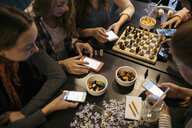 Tween girl friends playing chess, assembling jigsaw puzzle and texting with smart phones at table - HEROF16379