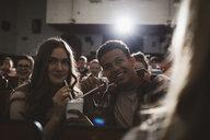 Tween couple watching movie, sharing soda with straws in movie theater - HEROF16394