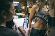 Tattoo artist with camera phone photographing bird tattoo on side of client - HEROF16430