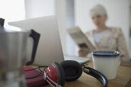 Woman reading newspaper at laptop behind coffee cup and headphones - HEROF16439