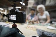 Smiling female fashion designers vlogging with digital camera in workshop - HEROF16448