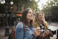 Smiling mature women friends with digital cameras on urban street - HEROF16463