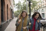 Smiling mature women friends walking arm in arm on urban sidewalk - HEROF16469