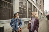 Smiling young women walking and talking on urban sidewalk - HEROF16481