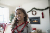 Smiling girl in Christmas Santa hat wrapped in red garland, looking away - HEROF16502