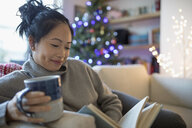 Smiling woman drinking coffee and reading book in Christmas living room - HEROF16511