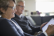 Smiling senior couple using digital tablet on sofa - HEROF16520