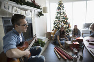 Smiling young man playing guitar while sisters wrap Christmas gifts in living room with Christmas tree - HEROF16565