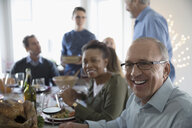 Smiling senior man enjoying turkey Christmas dinner with family at table - HEROF16568