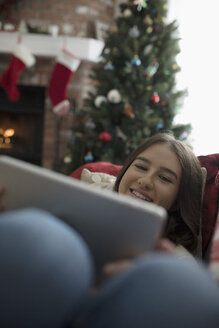 Smiling teenage girl using digital tablet in Christmas living room - HEROF16574
