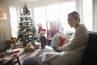 Smiling woman relaxing, drinking coffee and reading magazine in Christmas living room - HEROF16577