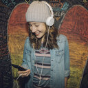 Smiling Caucasian tween girl with headphones and smart phone listening to music against wall with chalk wings - HEROF16586