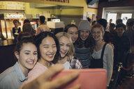 Smiling, happy tween girl friends taking selfie with smart phone in movie theater lobby - HEROF16592