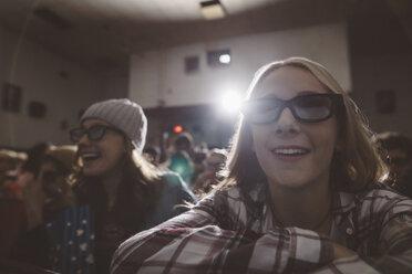 Smiling tween girl in 3d glasses watching movie in dark movie theater - HEROF16598