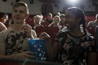 Smiling tween couple watching movie, sharing popcorn in dark movie theater - HEROF16601