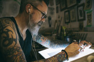 Tattoo artist listening to music and sketching at light table in dark tattoo studio - HEROF16634